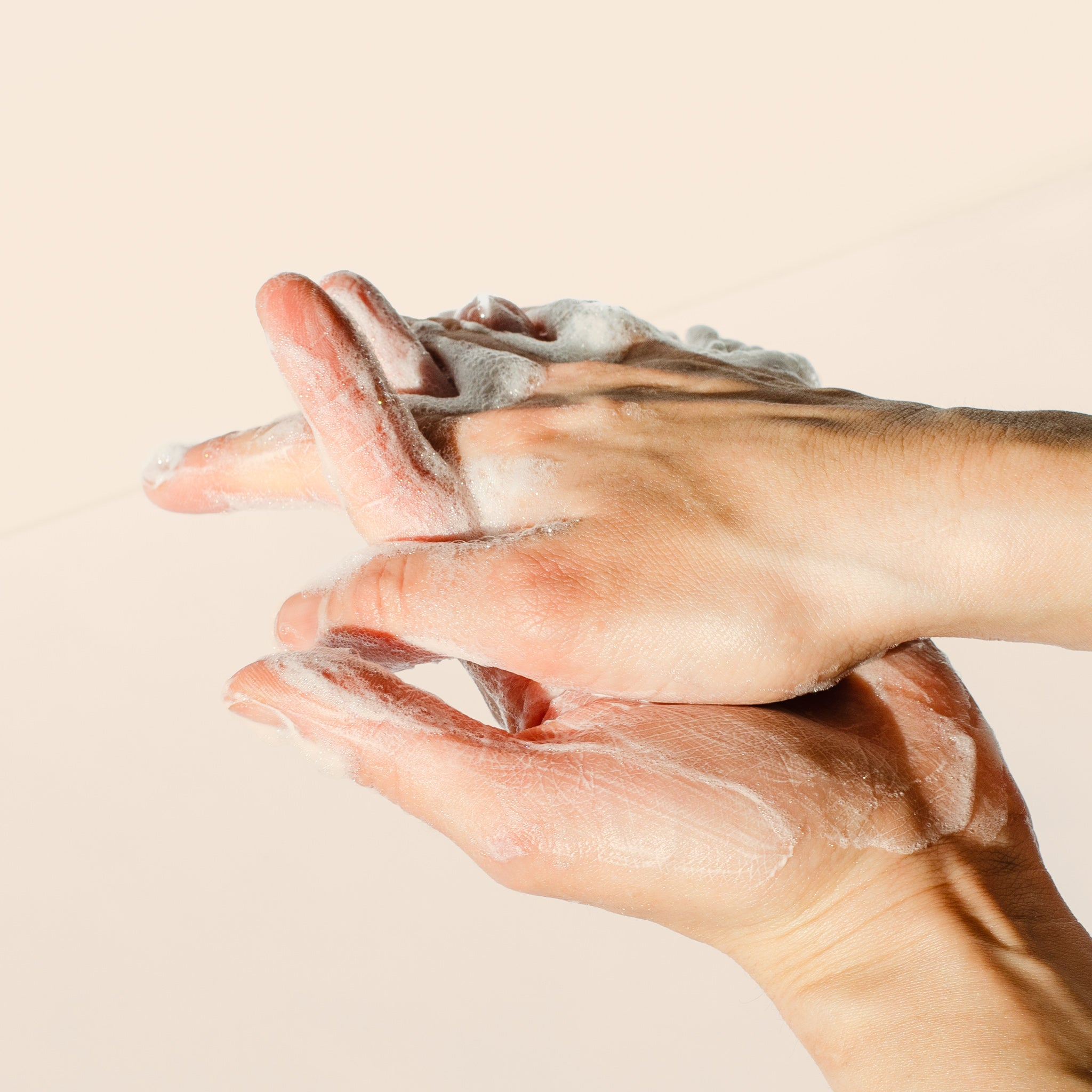 Image of hands washing with lather all natural liquid soap.