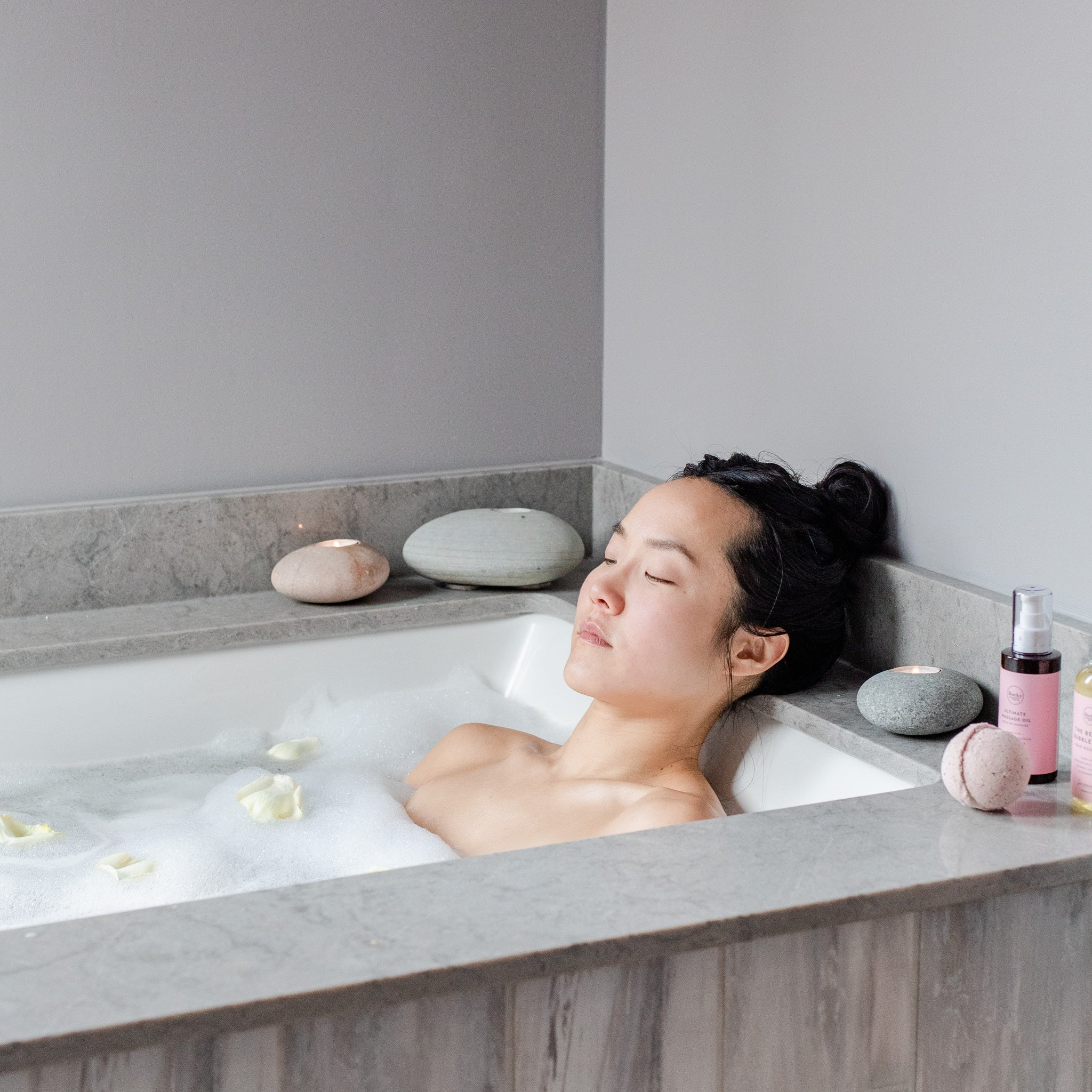 Woman relaxing in bath with natural rocky mountain soap massage oil.