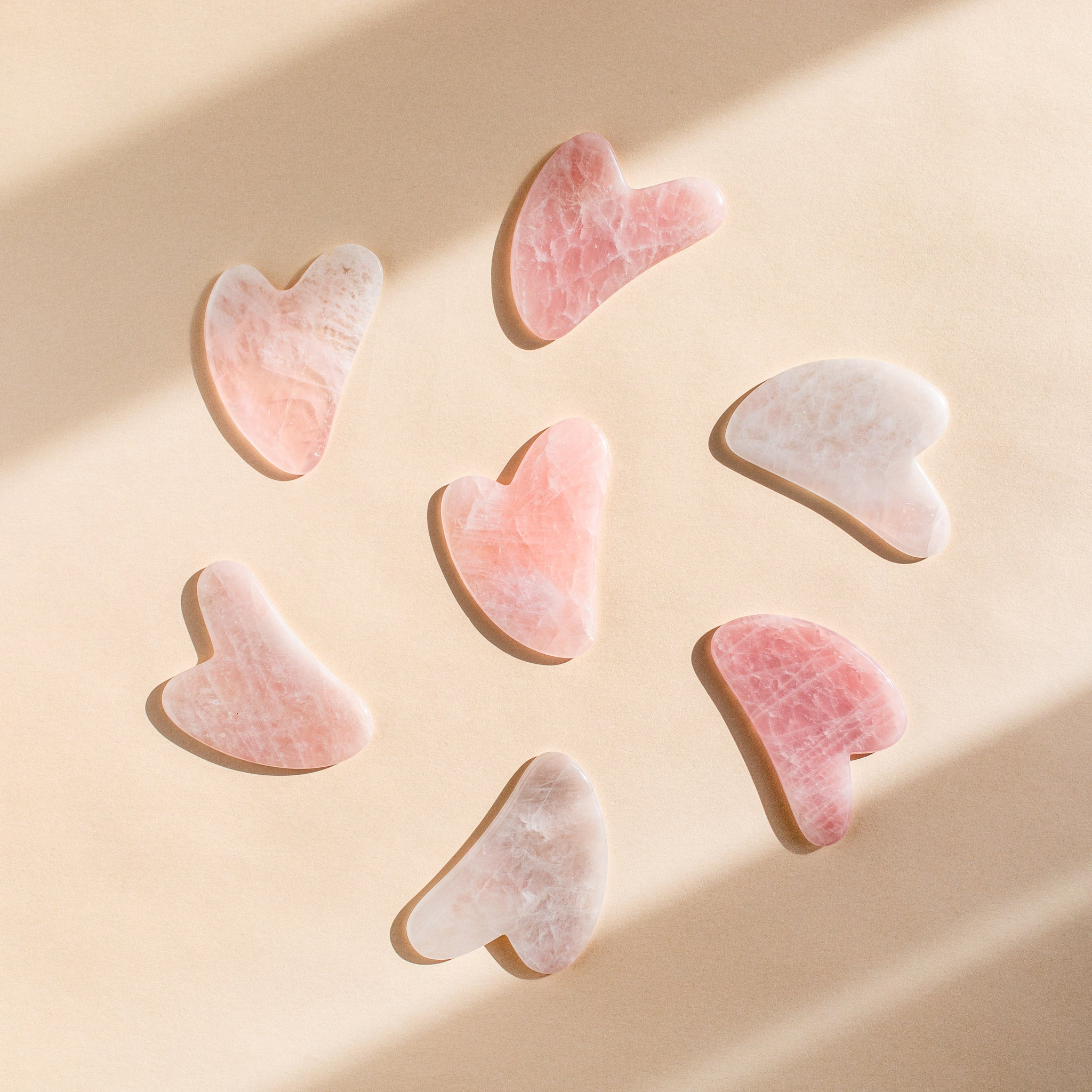 Image of rose quartz hand crafted gua sha tools in a circle.
