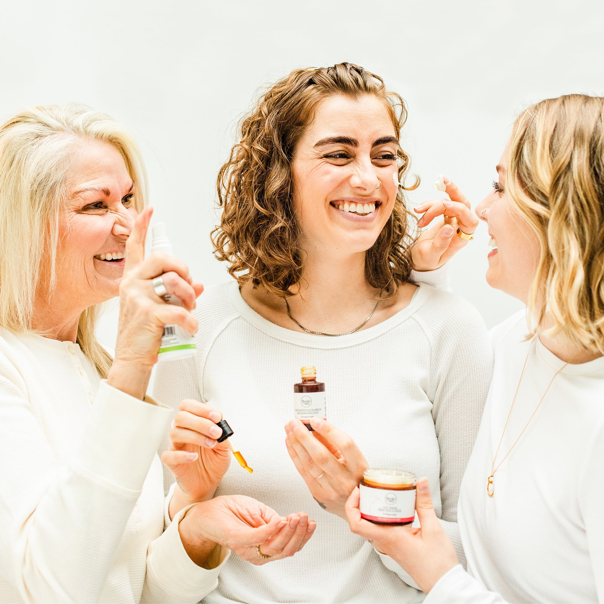image of three women of different ages using skin care products.