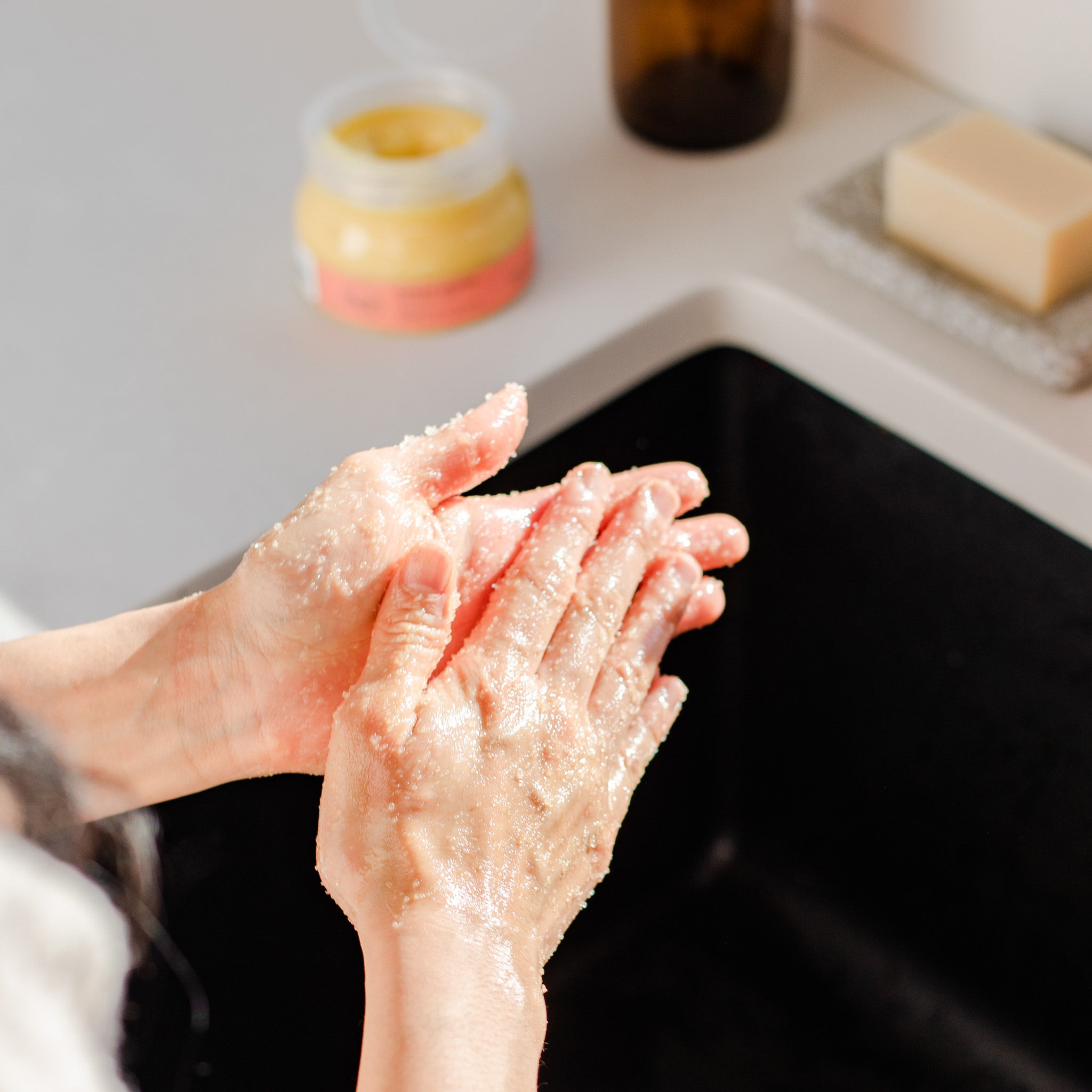 Image of all natural hand scrub from Rocky Mountain Soap Company being used to exfoliate hands.