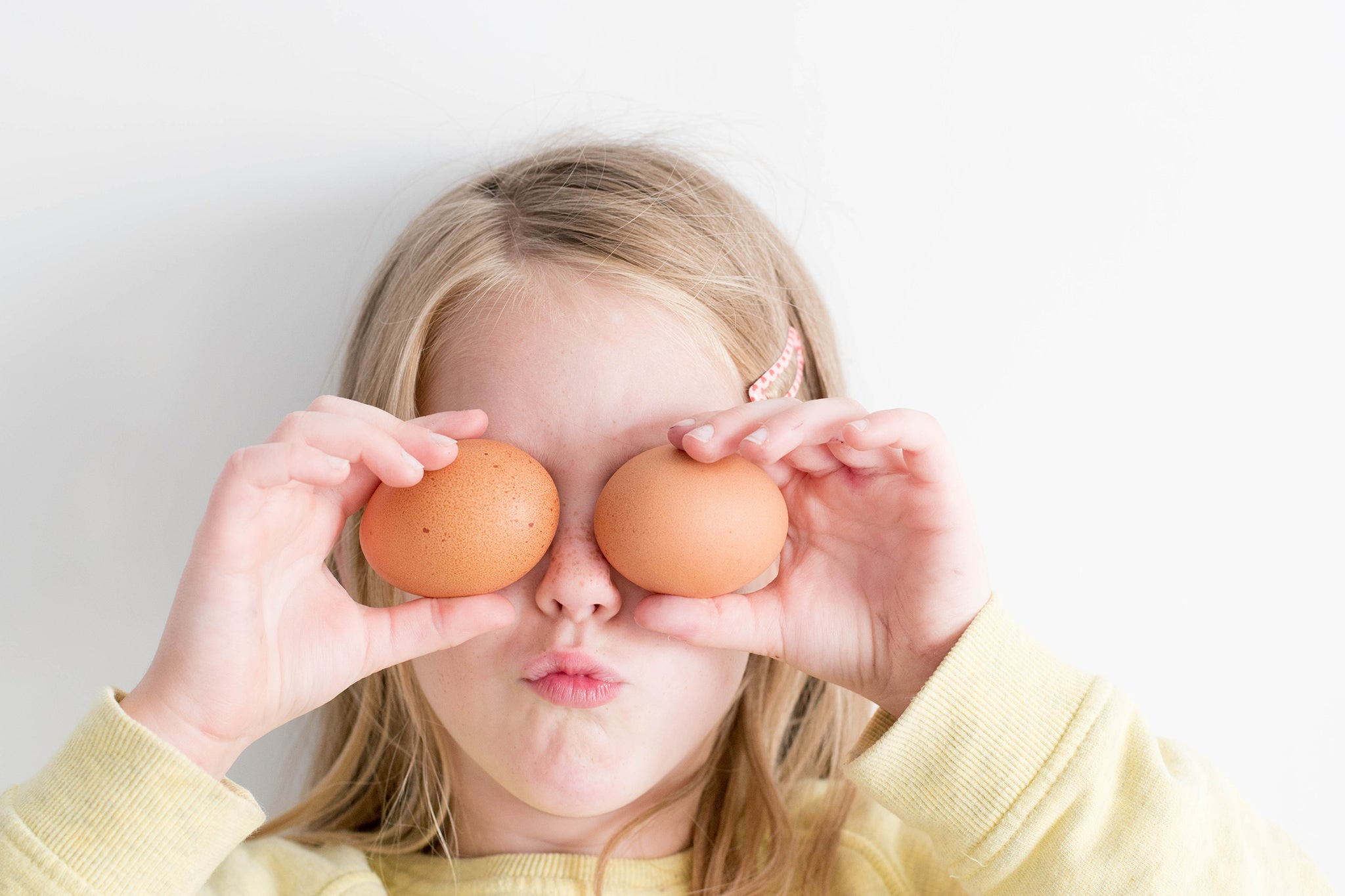 Image of little girl holding two brown shelled eggs over her eyes.