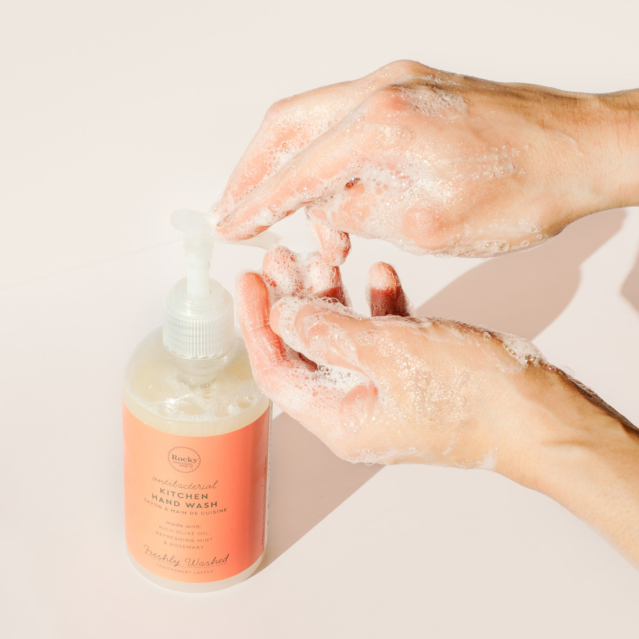 Image of hands washing with lather pumping antibacterial liquid soap from Rocky Mountain Soap Campany Kitchen Hand Wash.