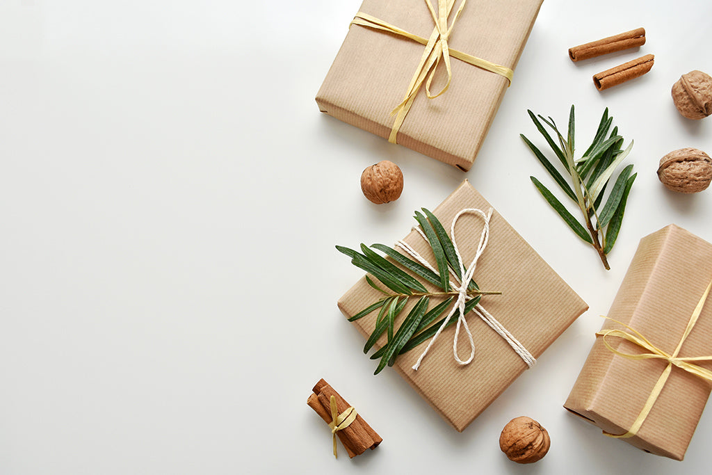 Gifts wrapped in plain brown craft paper are one way of using eco-friendly gift wrapping this season. Reusing interesting paper from around the home like old newspaper or maps are a way to keep less paper from the landfill.