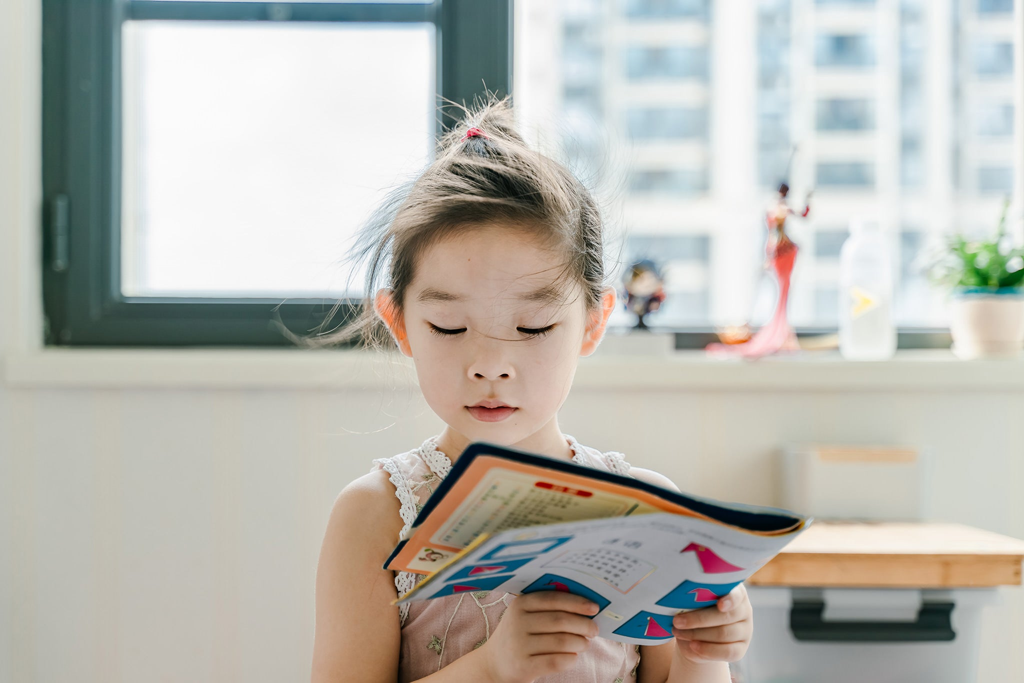 Image of little girl of asian descent reading a book.