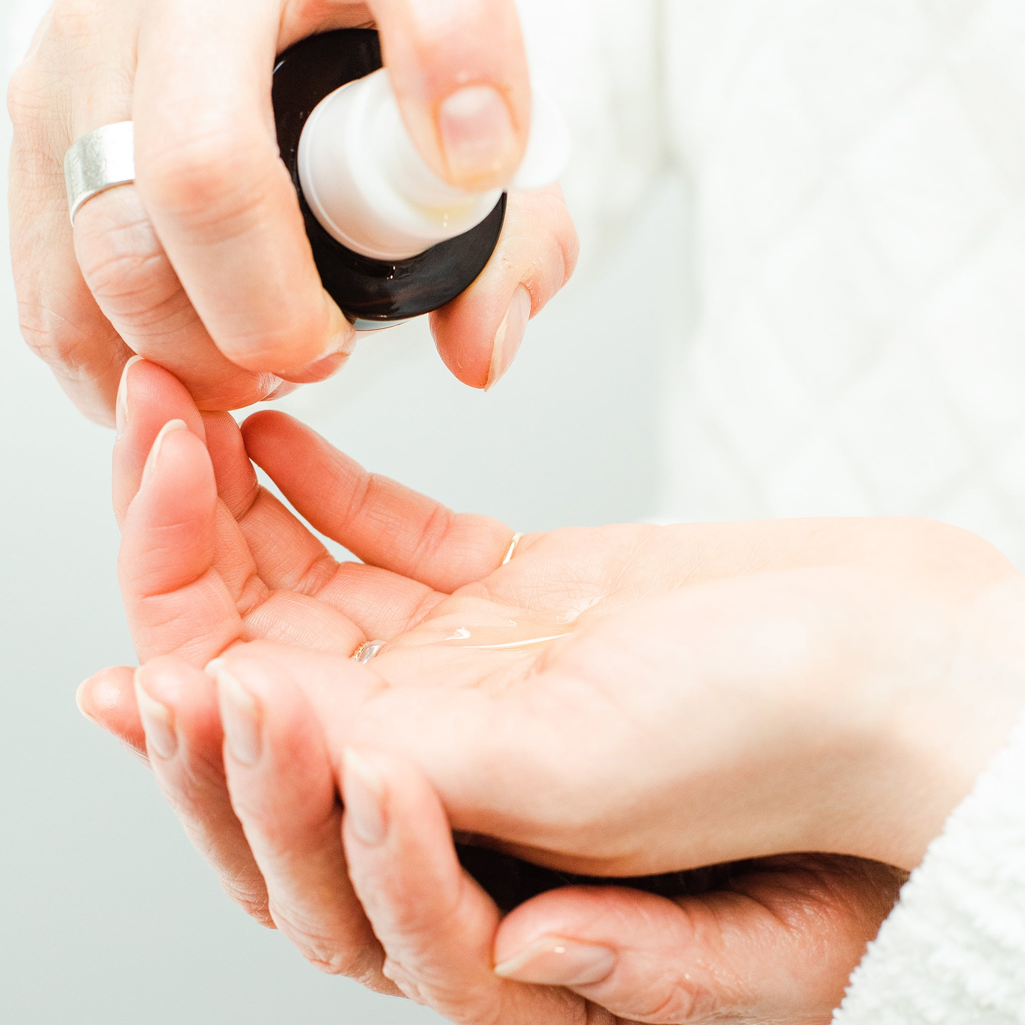 image of one hand pumping natural oil cleanser into the other hand.
