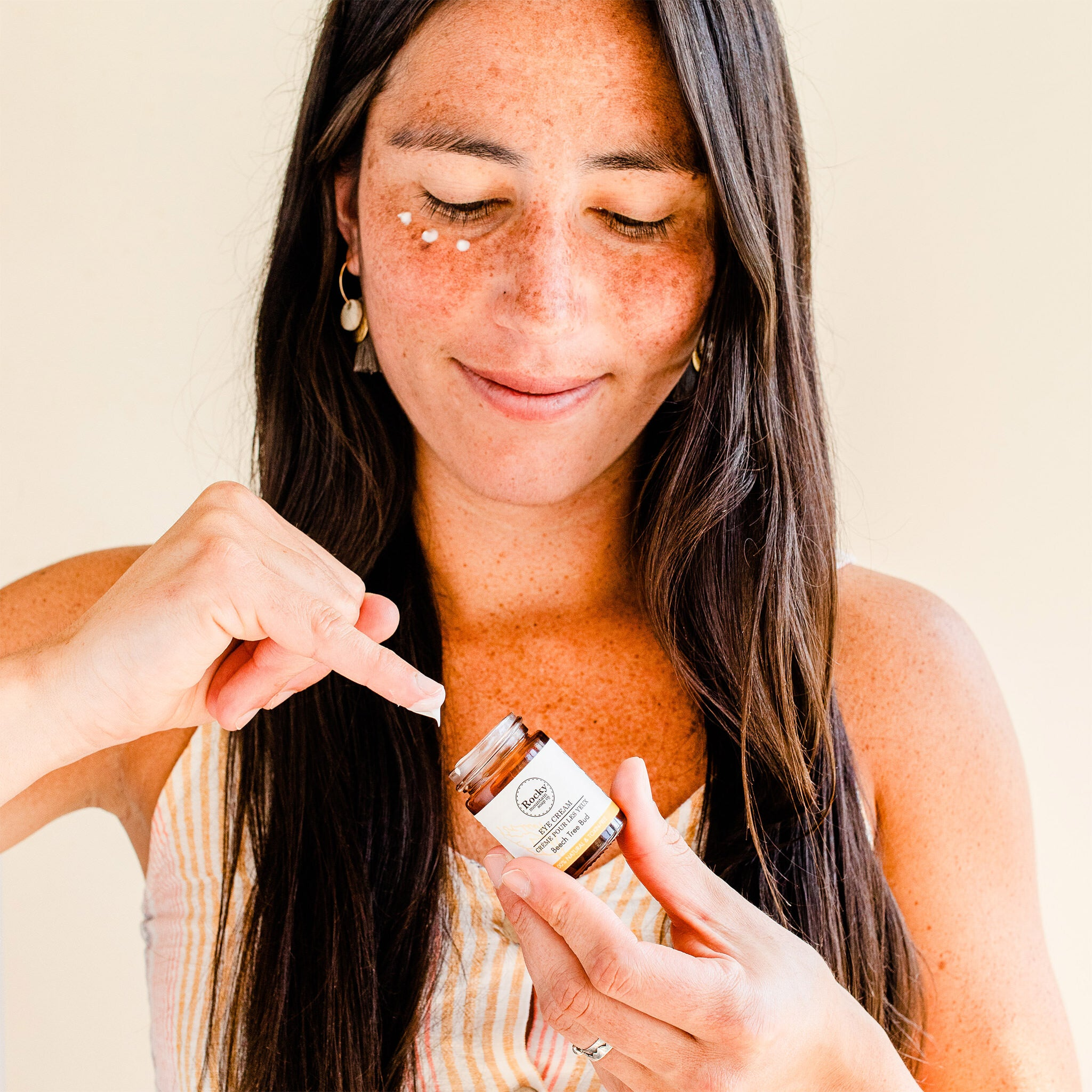 Image of woman applying natural eye cream from rocky mountain soap company.