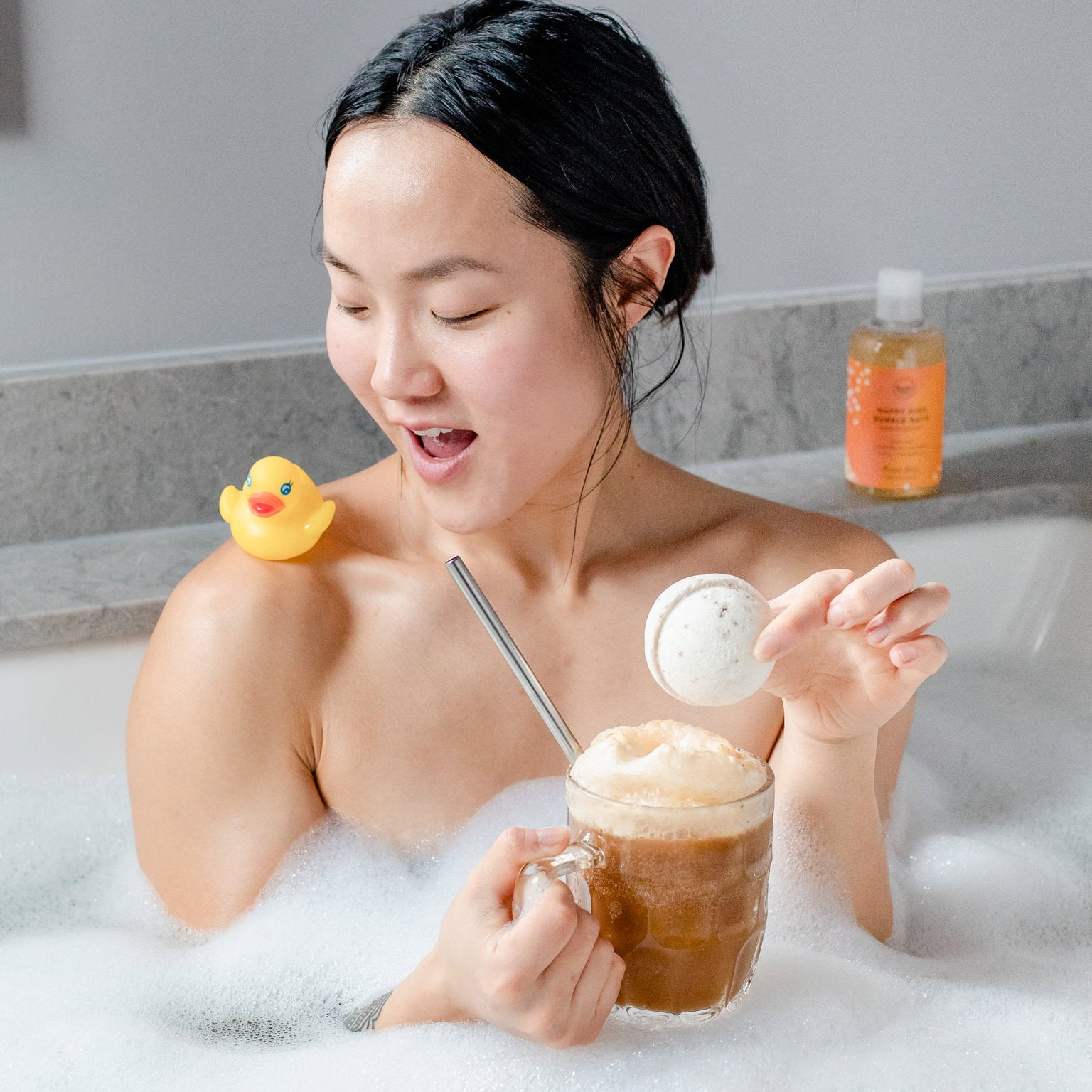 Woman in the bath drinking a root beer float holding a bath bomb with a bottle of all natural sls-free root beer scented bubble bath and rubber ducky in the background.