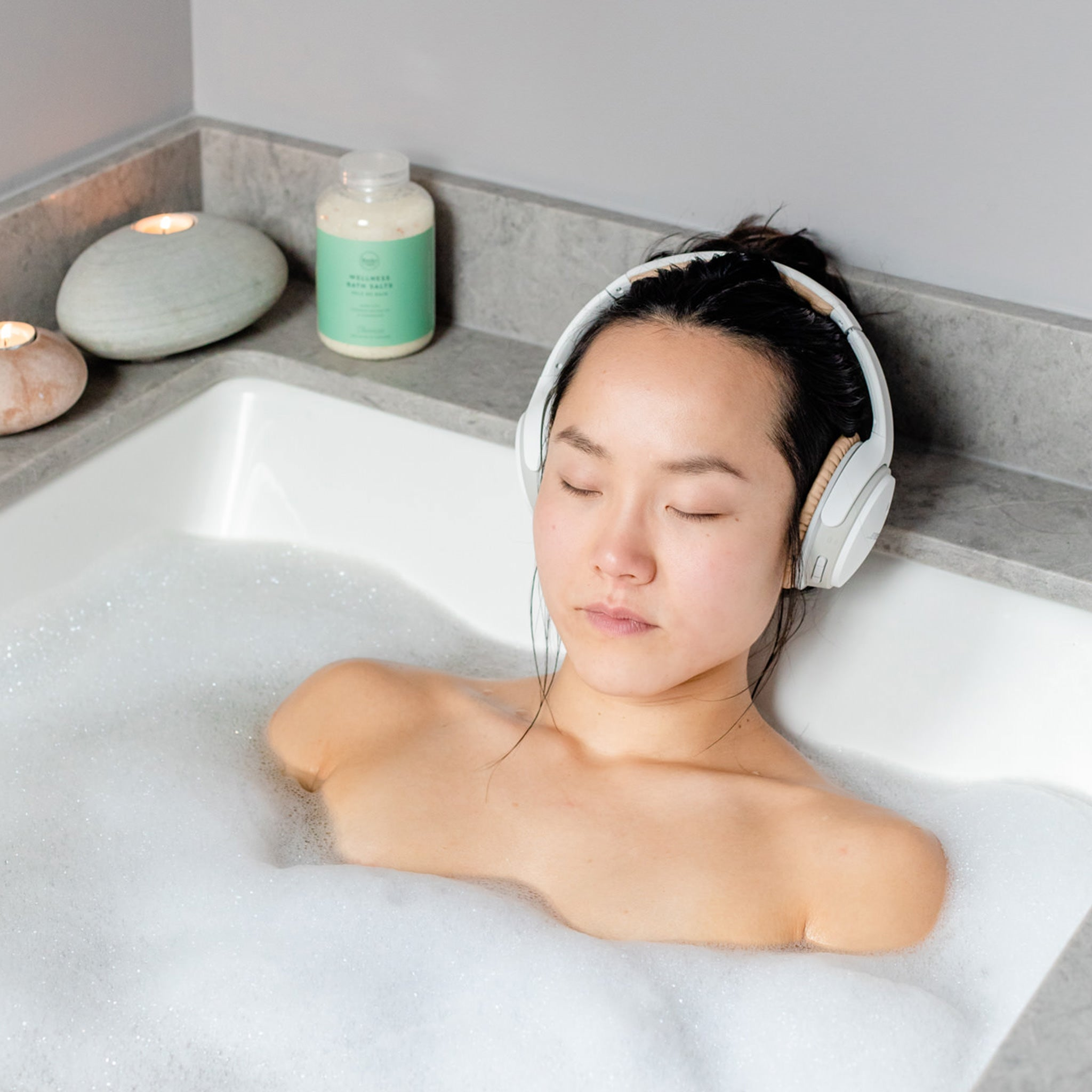 Woman in bath with headphones on, jar of all natural locally made Rocky Mountain Soap Company bath salts in the background.