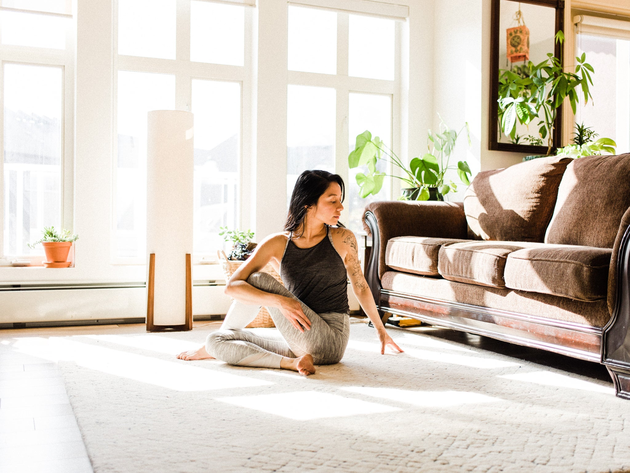Woman practicing yoga in her living room.