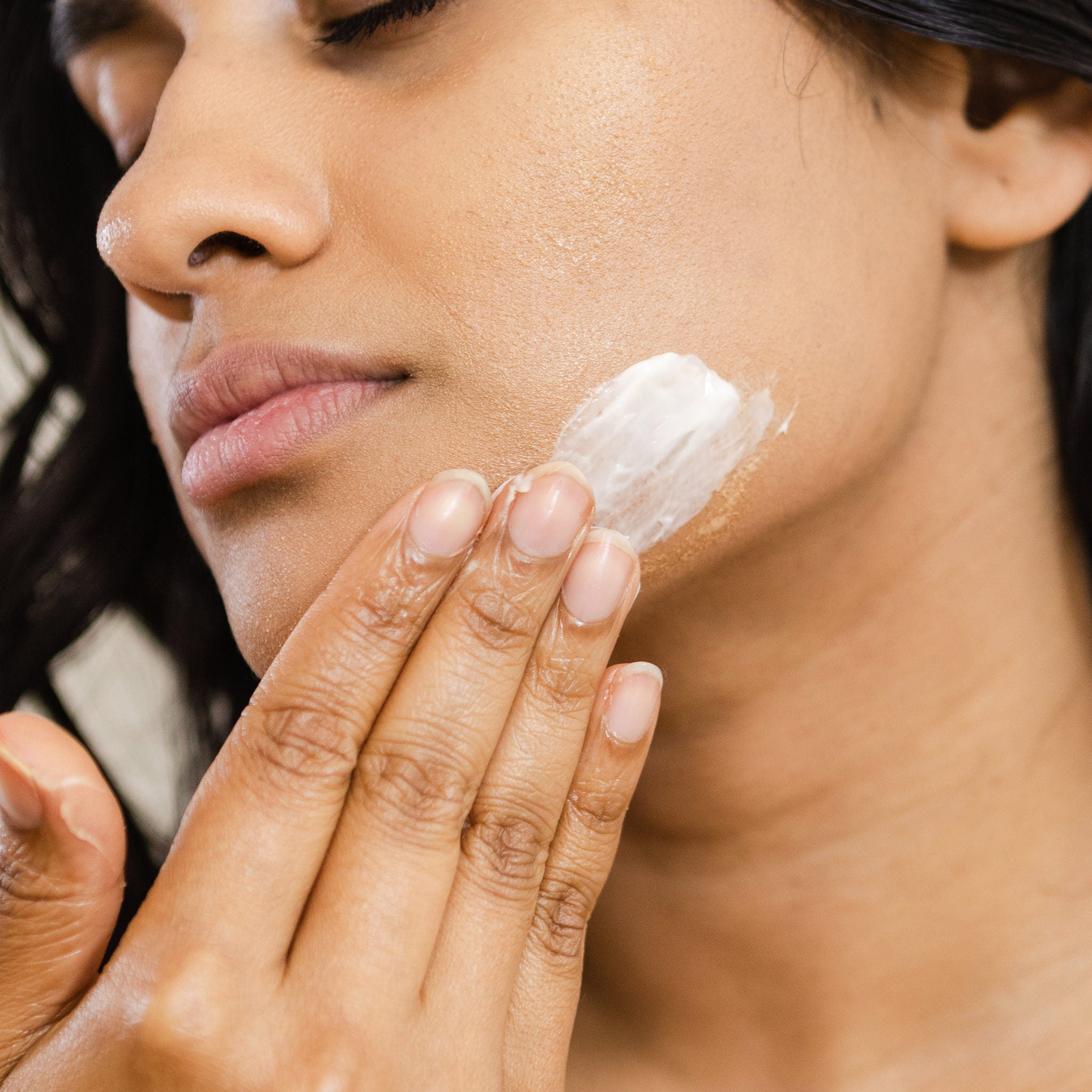 Image of woman putting moisturiser on their face.