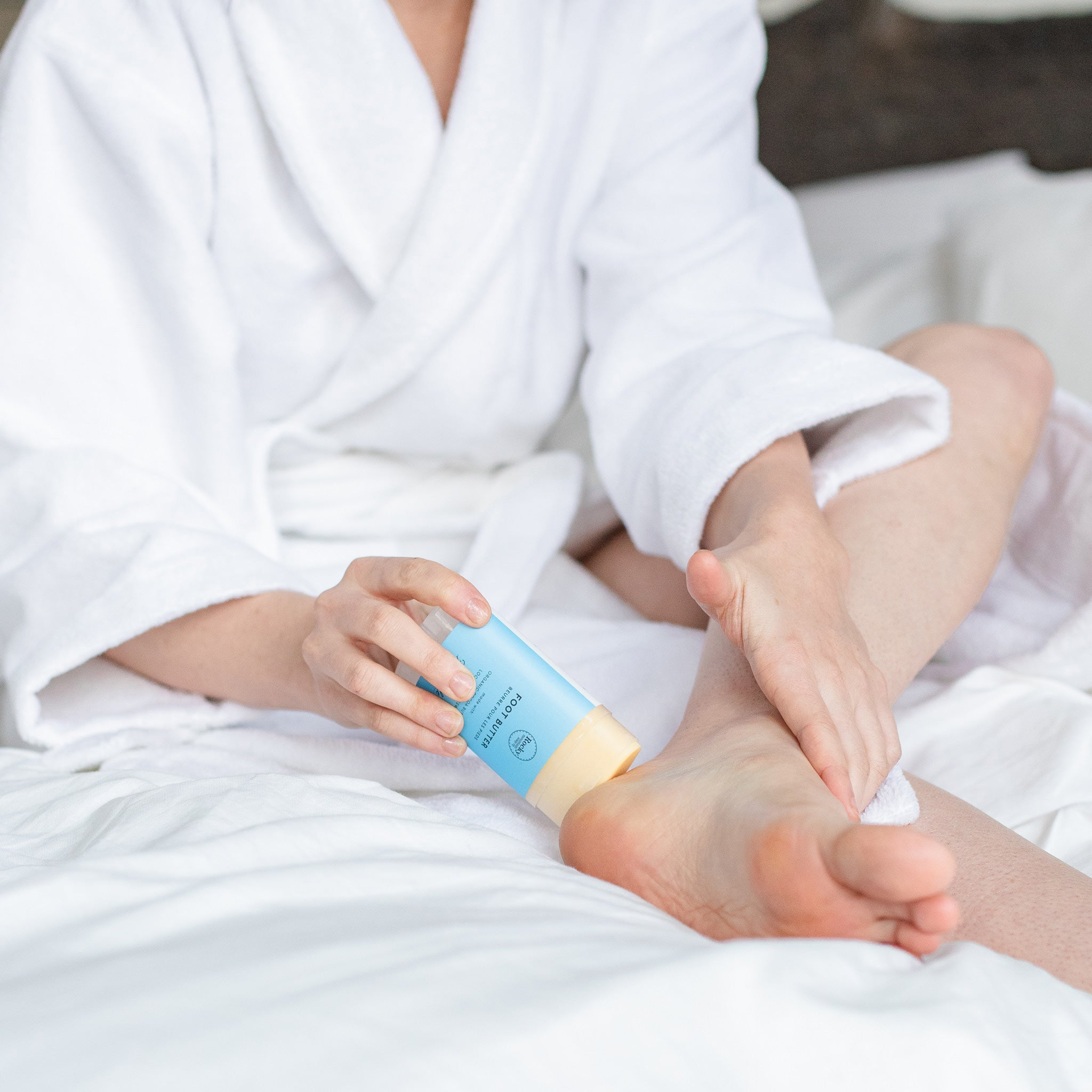 Image of woman in bath robe rubbing Foot Butter on her heel.