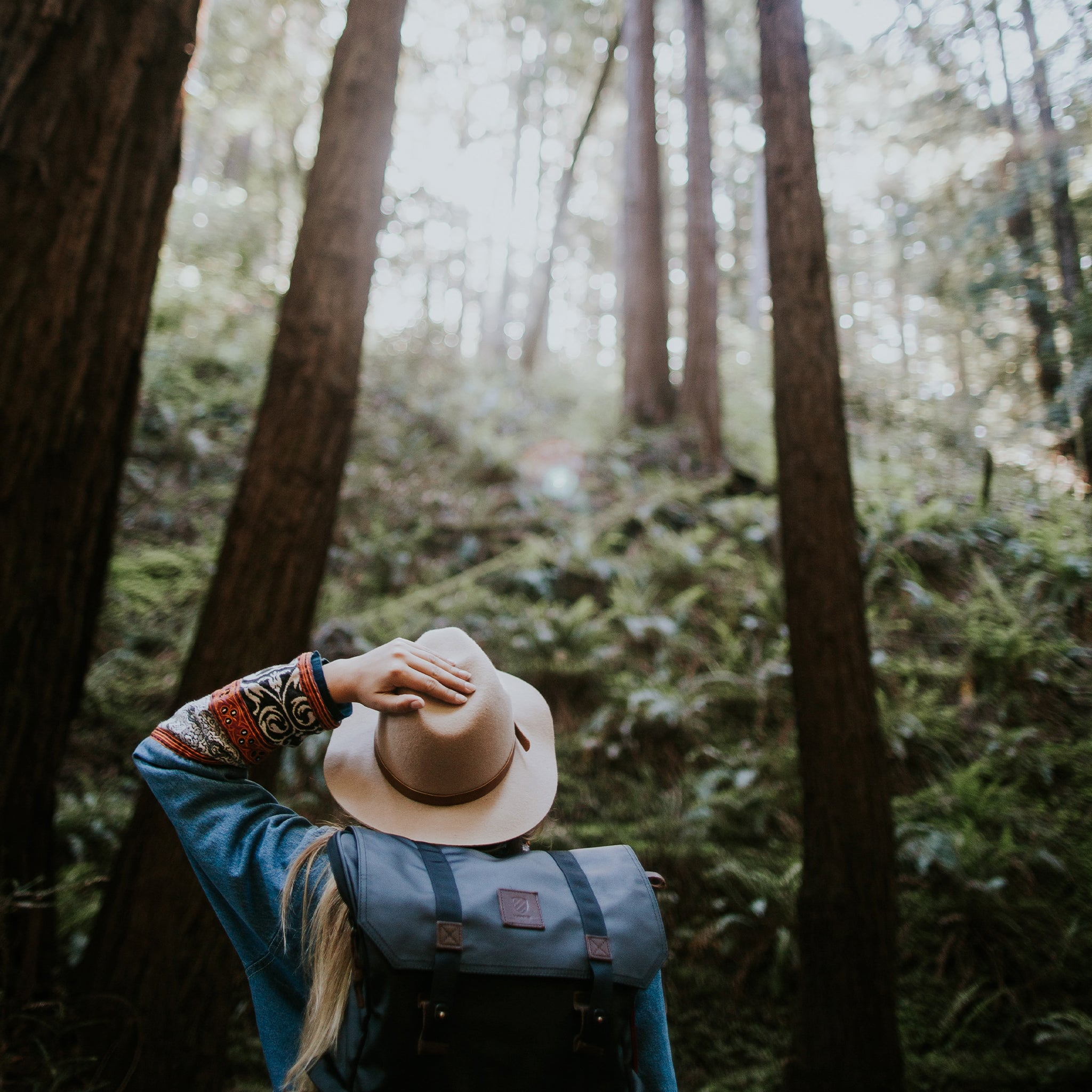 Woman hiking holding a hat.