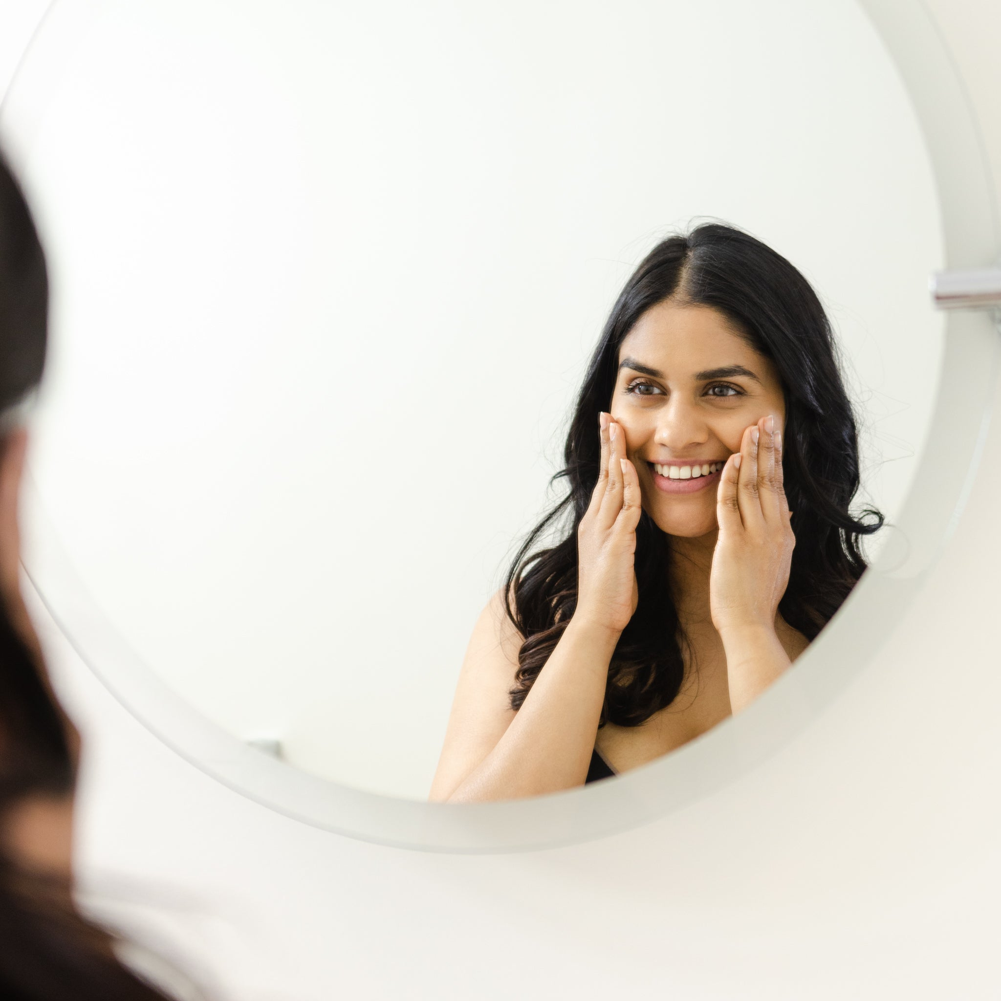 Woman holding her face looking into the mirror