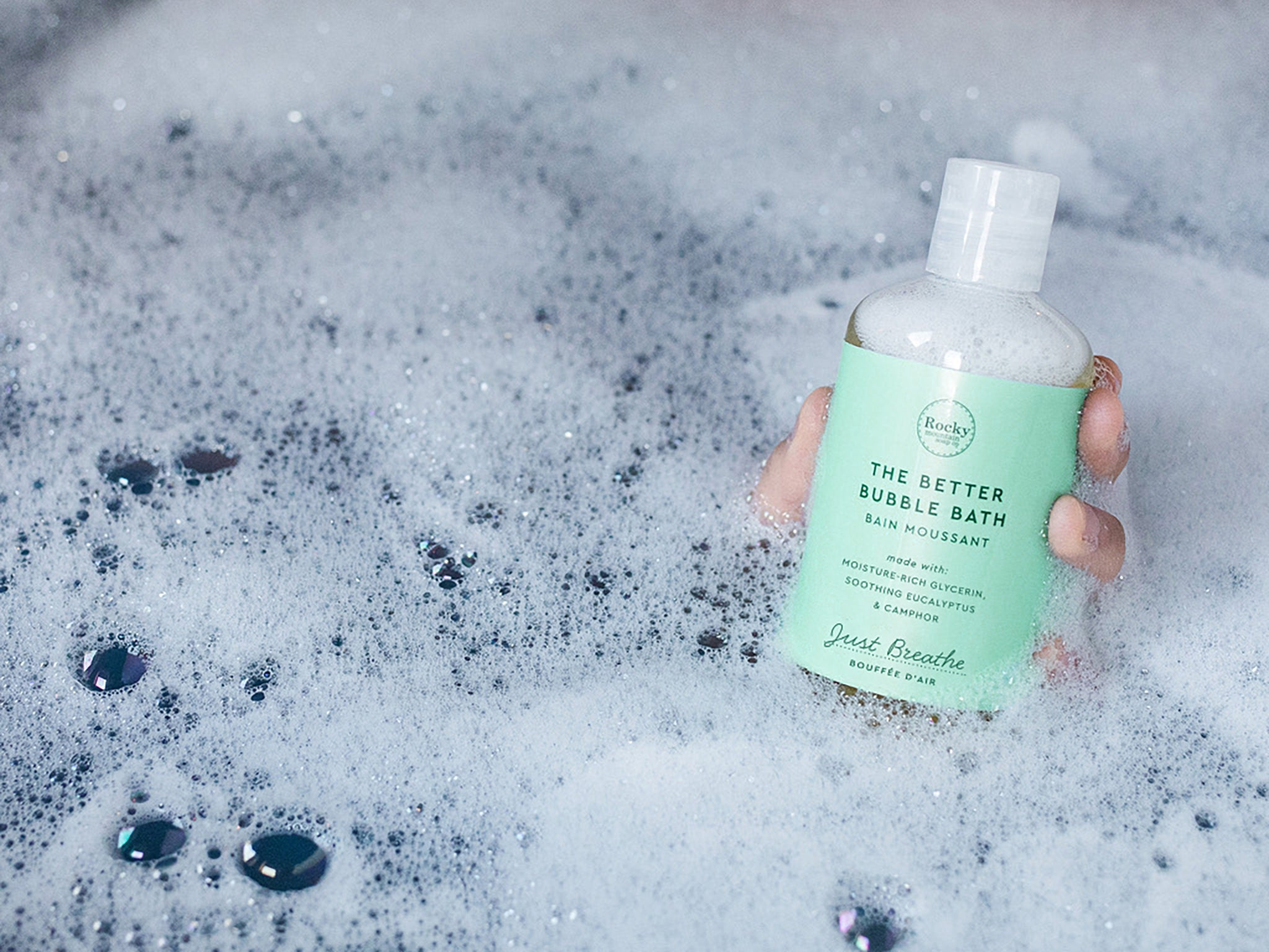 Image of hand holding natural bubble bath in tub surrounded by suds.