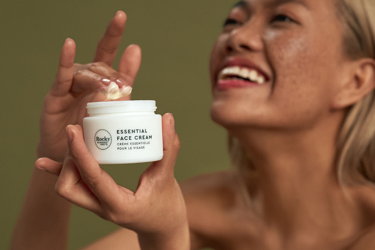 Image of woman using natural face cream that's made in Canada by rocky mountain soap company.