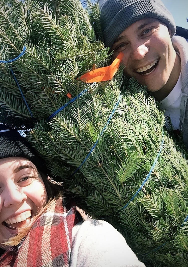 Carina and her partner holding a Christmas tree smiling at the camera.