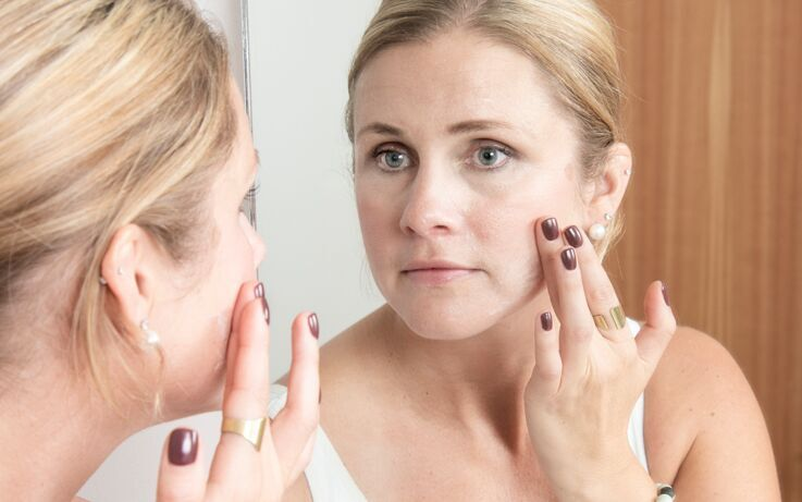 Woman applies face cream in mirror
