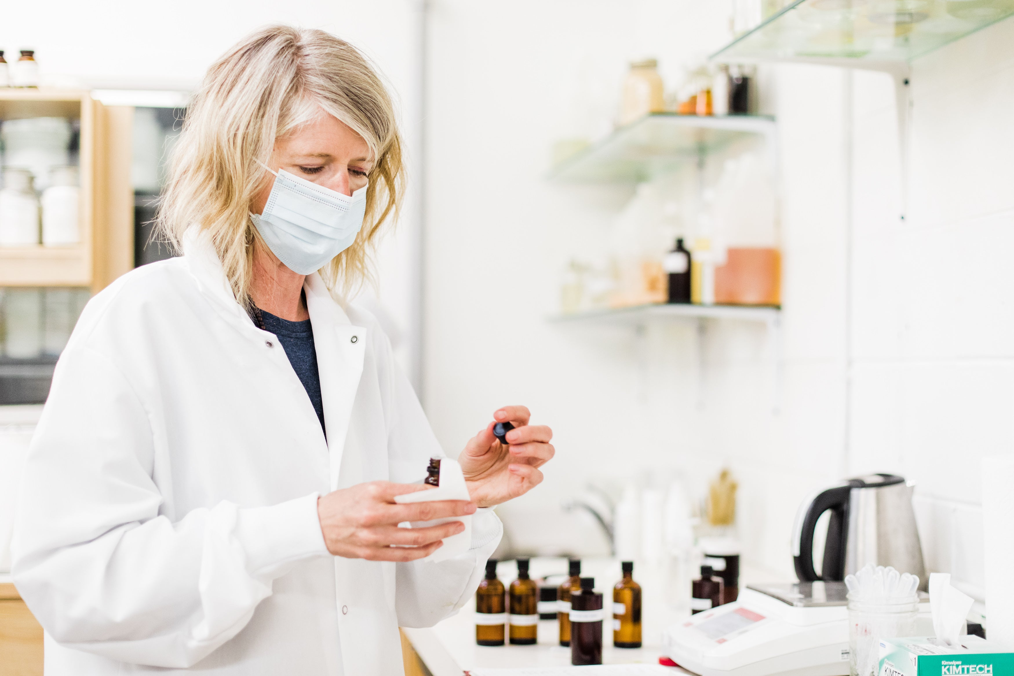 Image of woman in lab mixing essential oils.