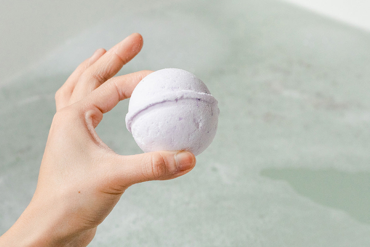 Image of natural bath bomb about to drop in bath.