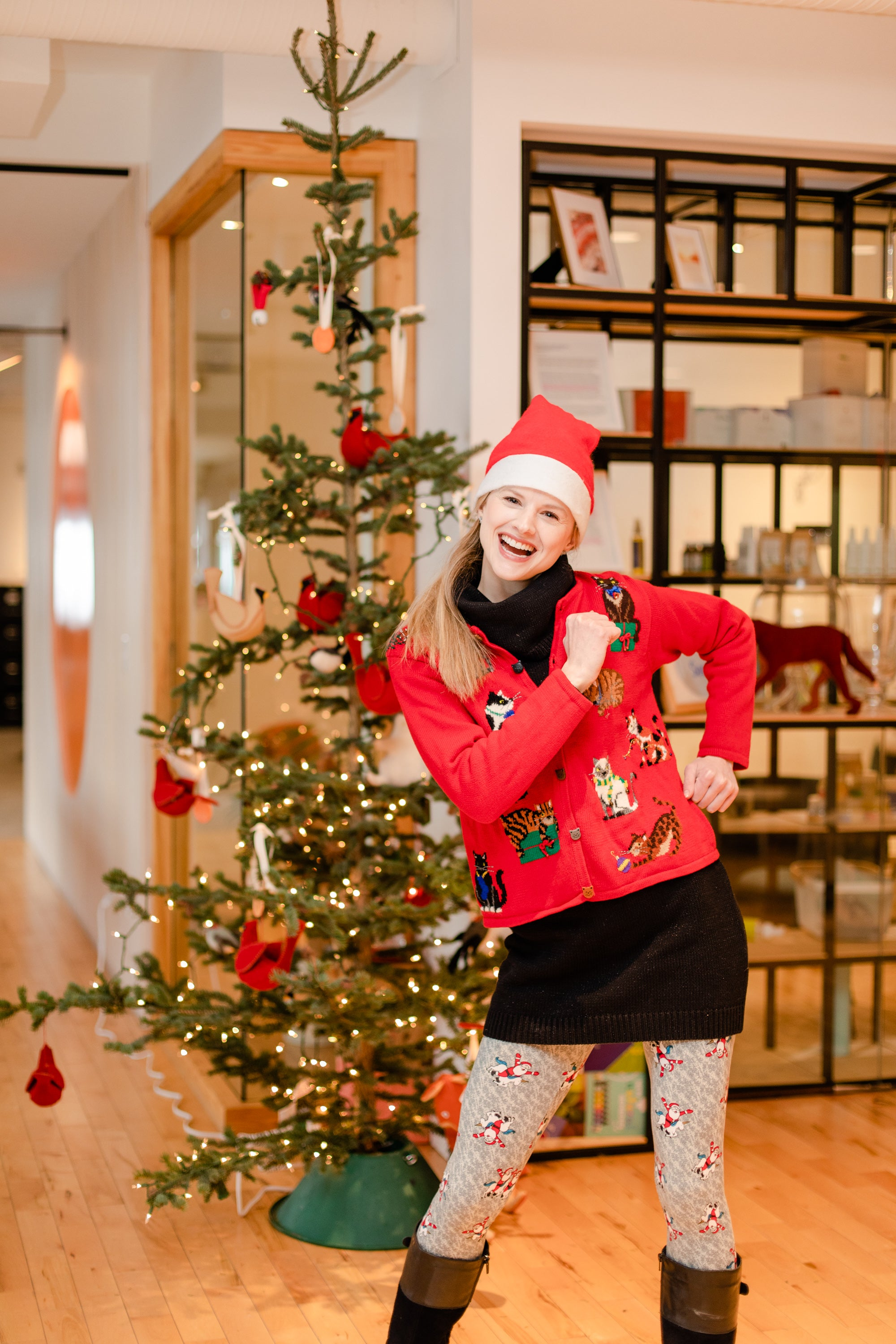 Sarah stands in front of the Rocky Mountain Soap Company holiday tree in a holiday sweater and Santa-themed nylons.