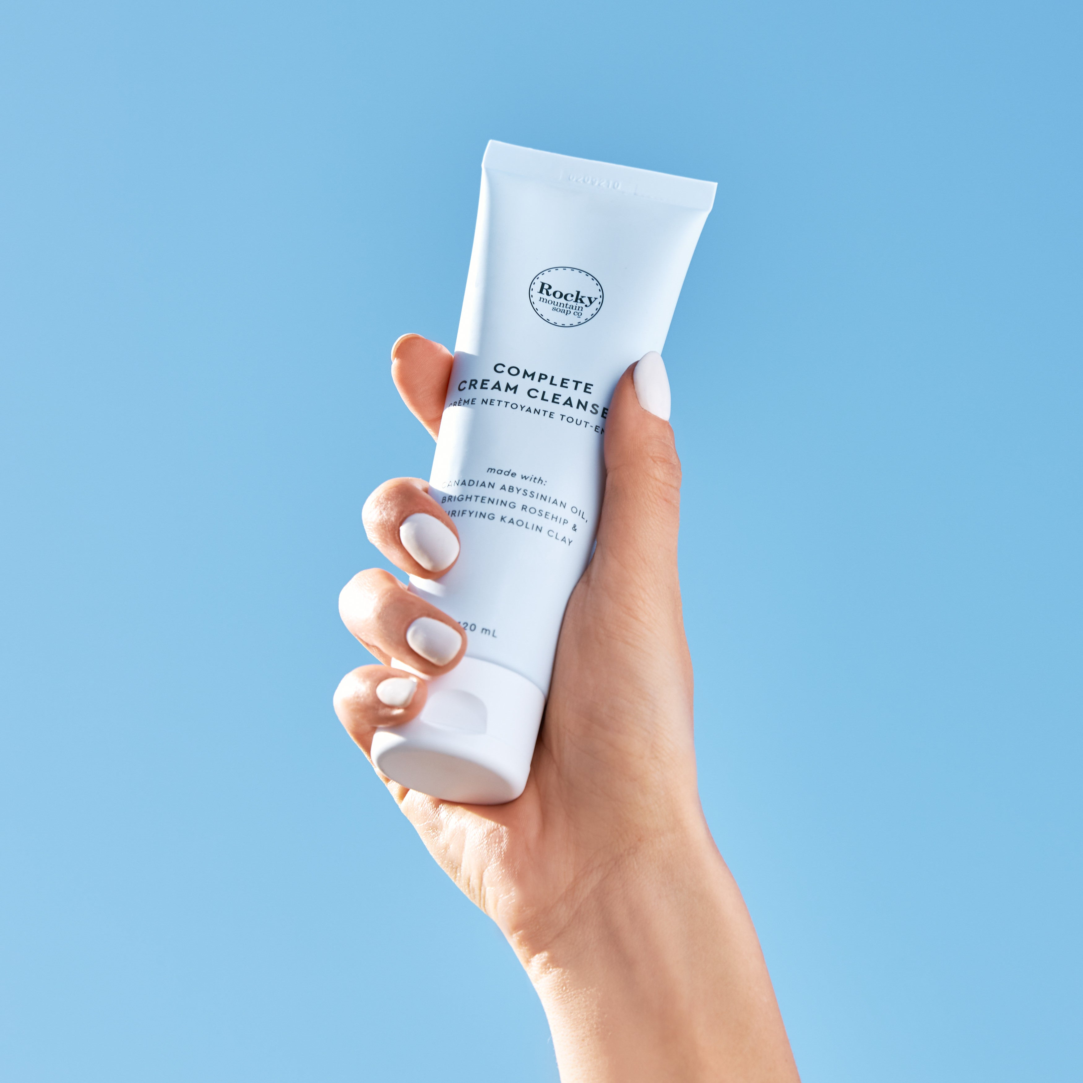 Image of natural cream cleanser being held up to the sky.