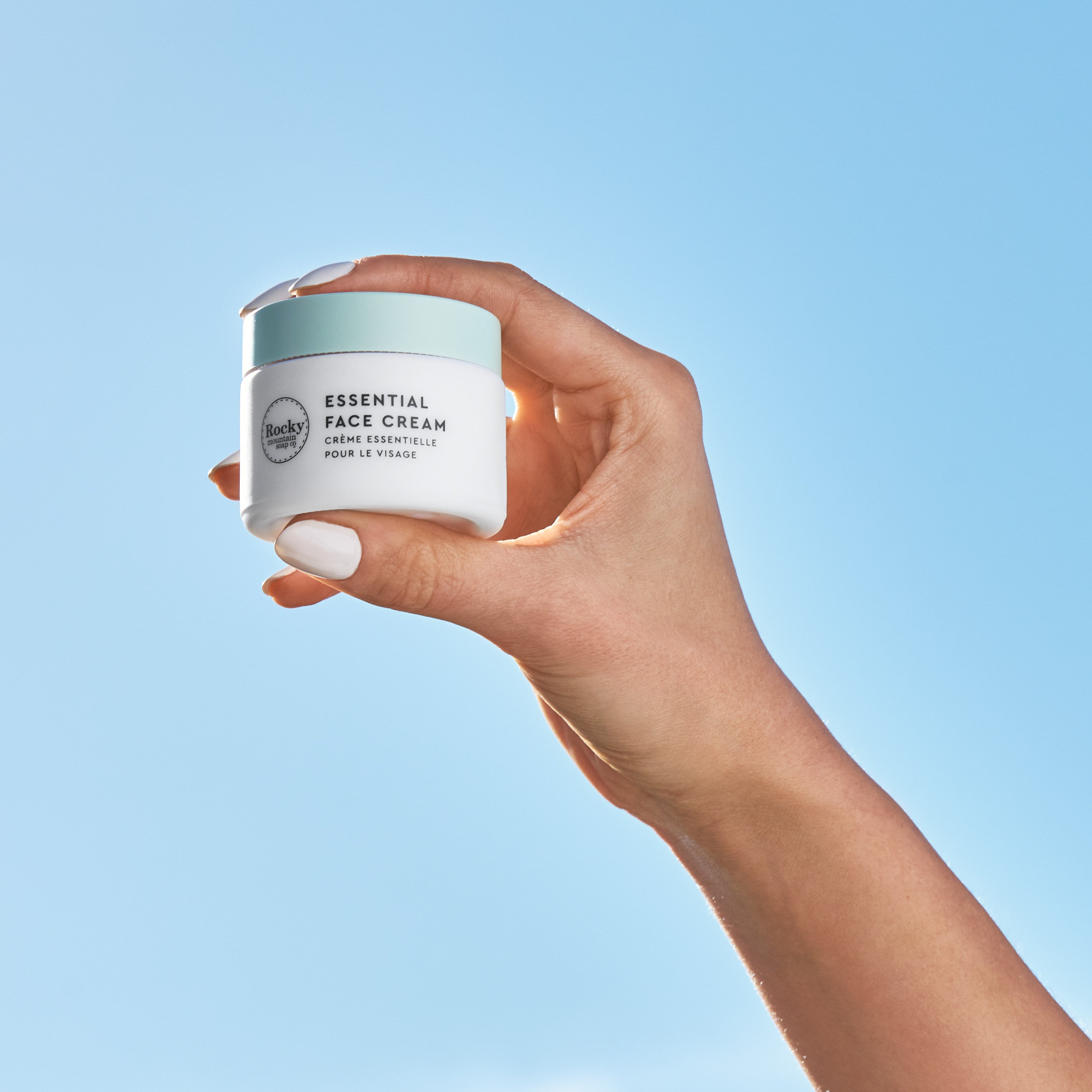 Image of natural face cream being held up to the sky.