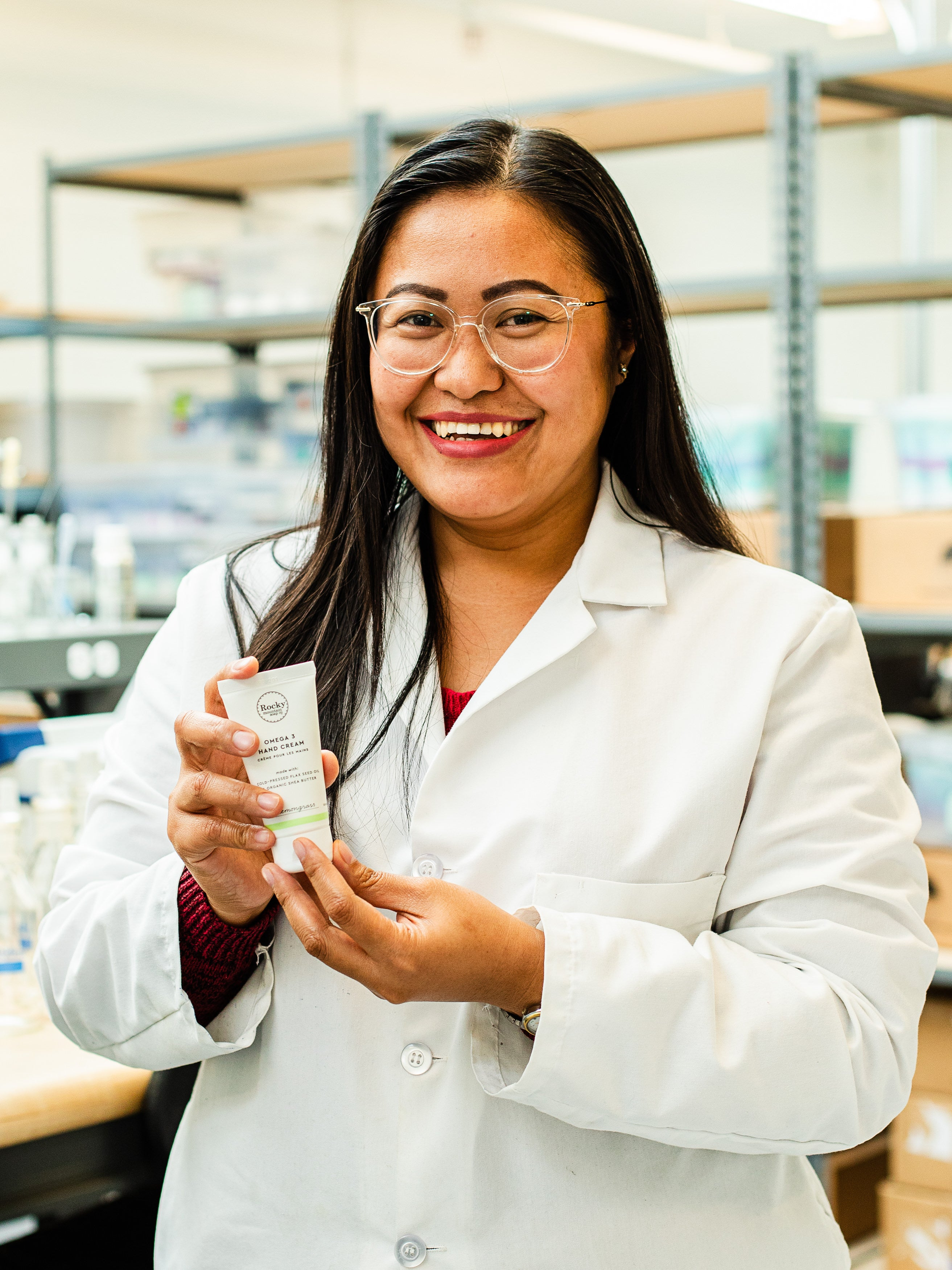 Image of woman in a lab coat holding a Lemongrass Hand Cream from Rocky Mountain Soap Company