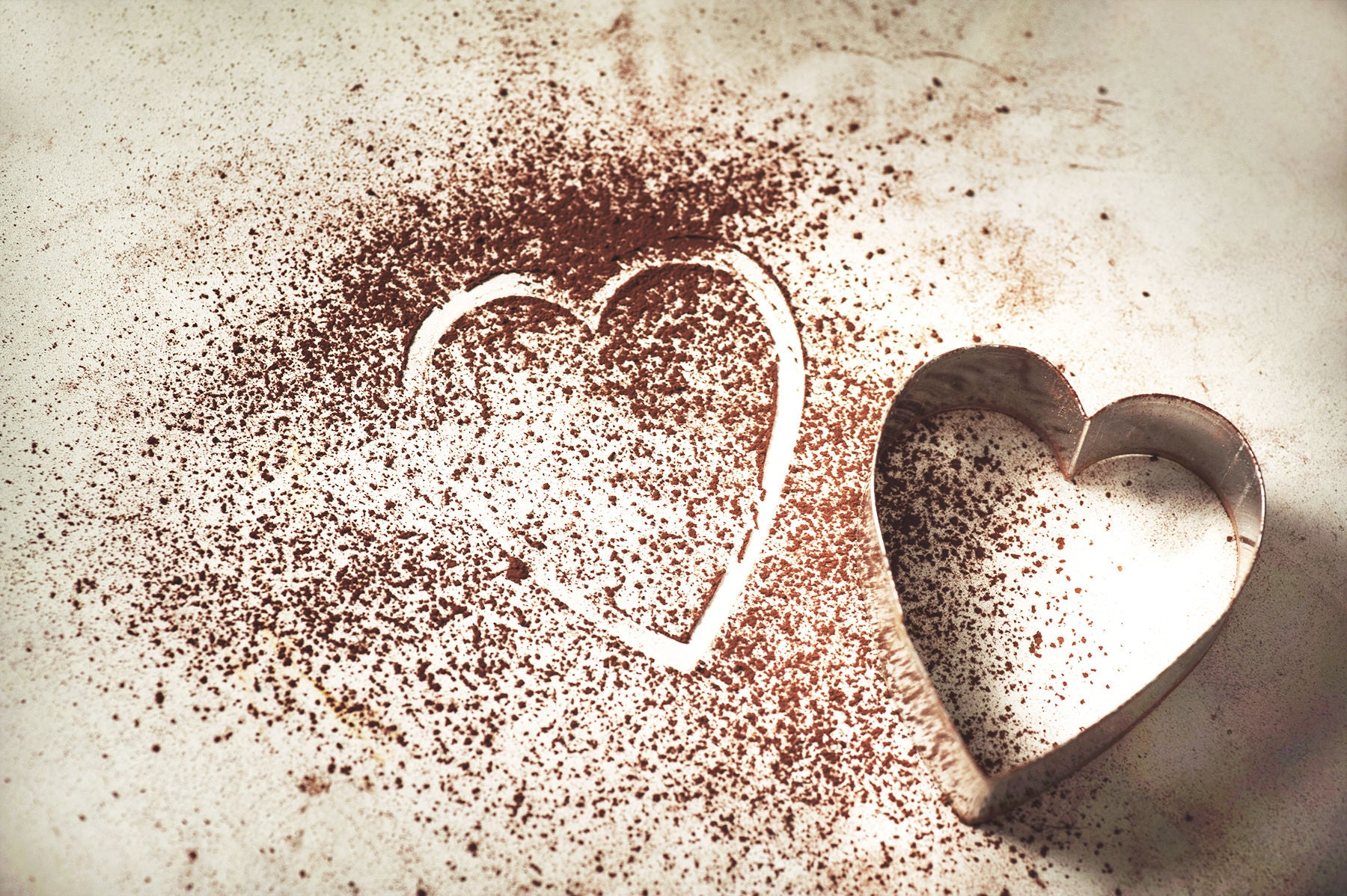 Cocoa powder with a heart shape in the powder from a heart shaped cookie cutter that is next to the cocoa powder.