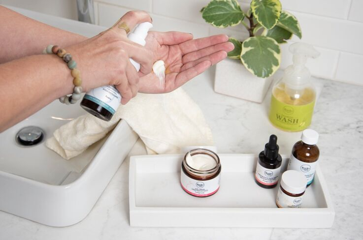 Bathroom sink with face cream and oil in palm of hand