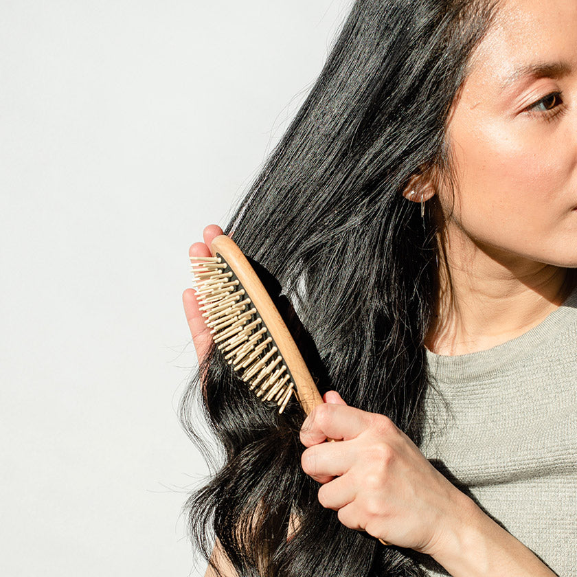 woman using a wooden hair brush to brush her dark brown hair.