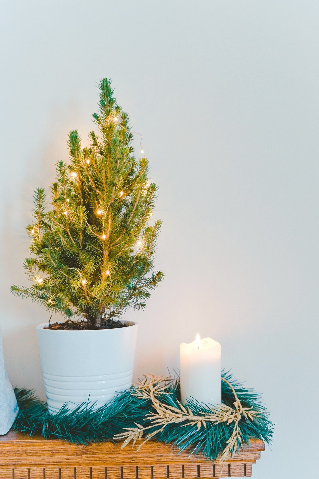 A small Christmas tree and candle create a festive atmosphere on the mantle when getting your home ready for the holidays.