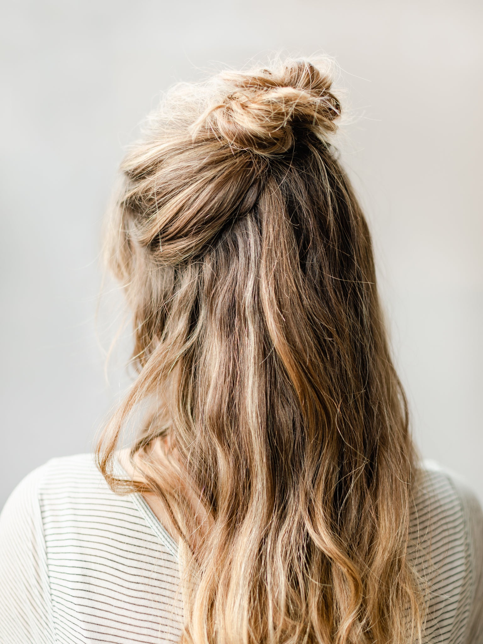 Hair half up in a top knot bun for a sleek easy holiday hairstyle look.