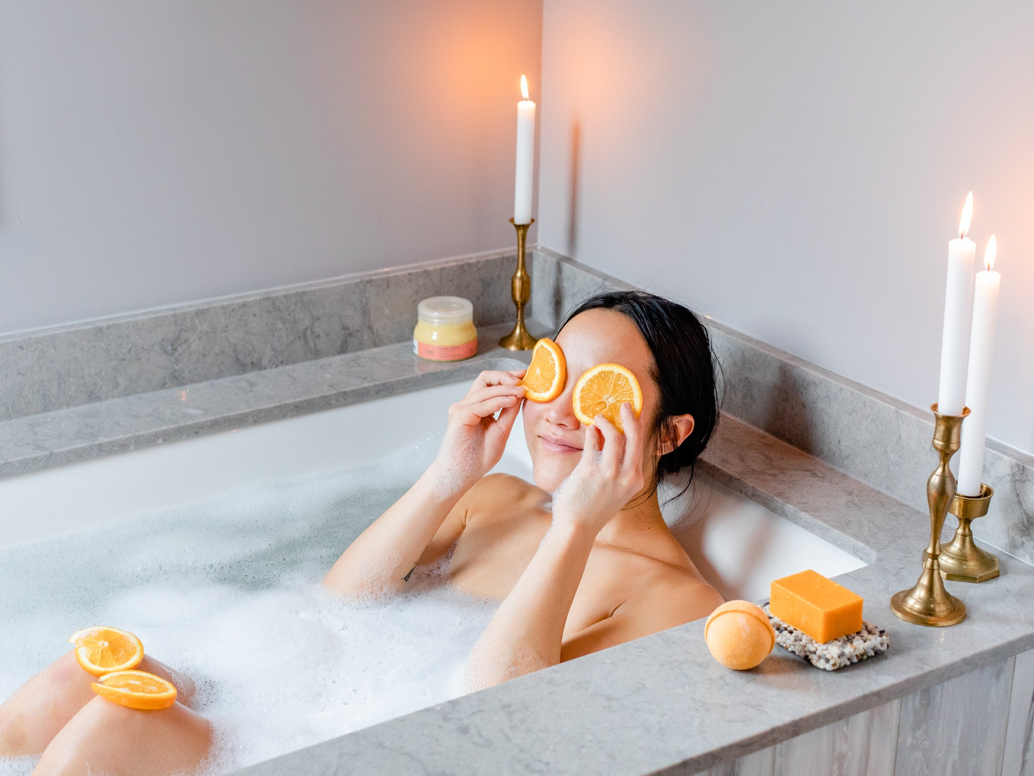 Woman in the bath with candles on the side of the tub and two orange slices over her eyes.