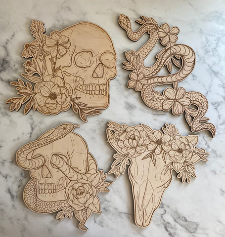 Four engraved pieces of wood art - top left skull with flowers, top right snake with flowers, bottom left skull with a snake coming out of the eyes, bottom right deer skull with flowers on top of the antlers. Wood is a light color and the details are engraved in dark brown. Backdrop is white and grya marble.