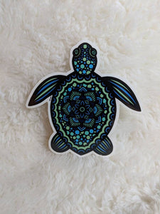 This particular sticker features a sea turtle filled with polka dots and patterns. The turtle is various shades of blue, teal, and sea foam green. The turtle has a thin white cut-line around the design and a glossy finish.