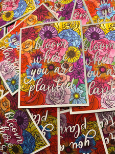 "Close up on a pile of stickers. They are all the same, they are rectangle in shape and feature colorful pink, purple, blue, orange, red, and yellow flowers. There is white text overtop of the flowers in script writing that says ""Bloom Where You Are Planted"" in lower case writing. The stickers have a thin white outline and a slight metallic shift."