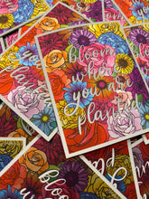 "Load image into Gallery viewer, A close up of a pile of stickers - all the same. They are rectangle shaped  and the design is a collage of flowers in various colors - pinks, blues, purples, yellows, oranegs, and reds. There is lowercase script text that says ""bloom where you are planted"" in a white font with a slight black drop shadow. The sticker has a small white border around the design."