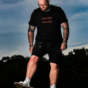 soulvalleytribe anxiety killer black tee with red font on male model riding skateboard
