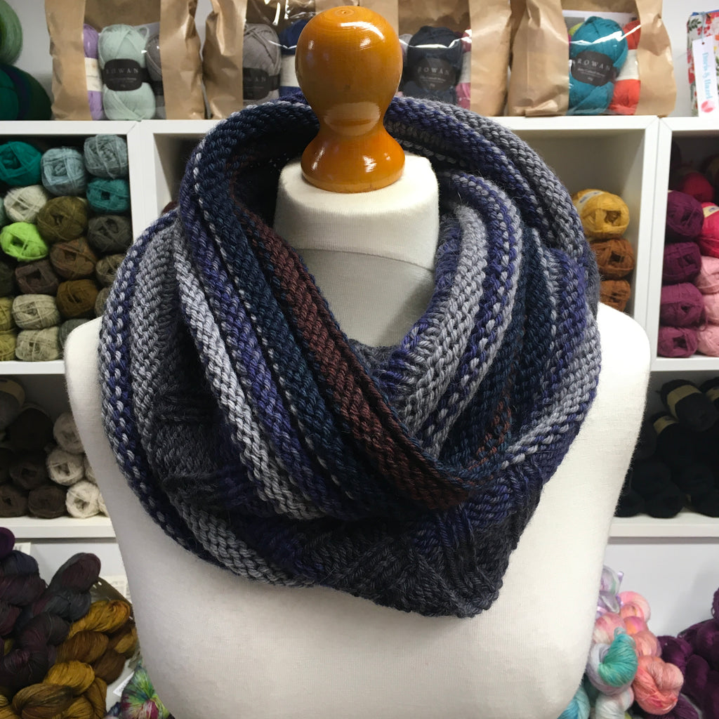 very long cowl in dark greys and blues looped thrice around mannequin neck