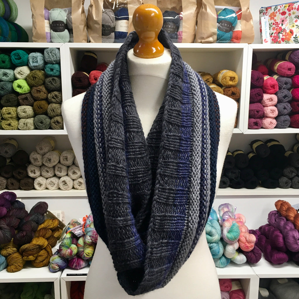 long narrow cowl in shades of grey and blue on a mannequin
