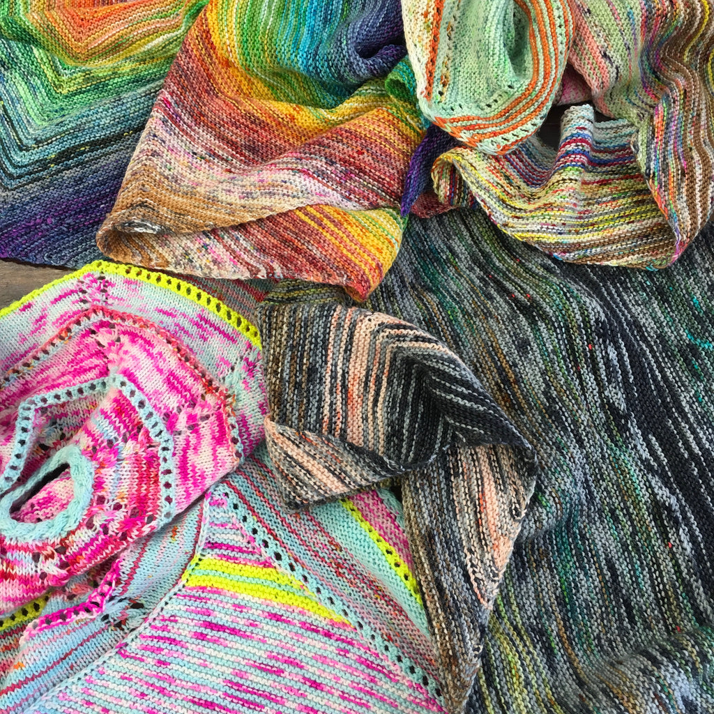 pile of multicoloured shawls knitted in my mama knits hand dyed yarn