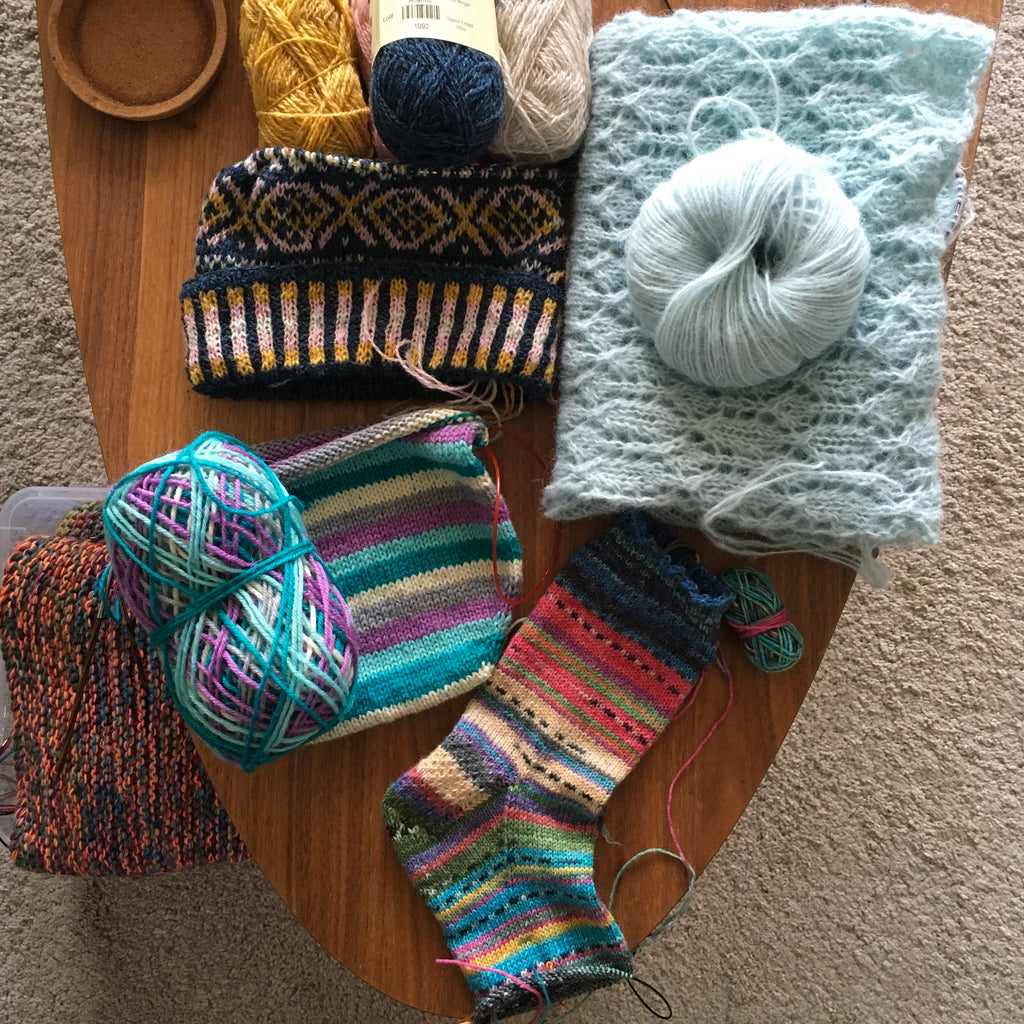 coffee table filled with unfinished hand knitting