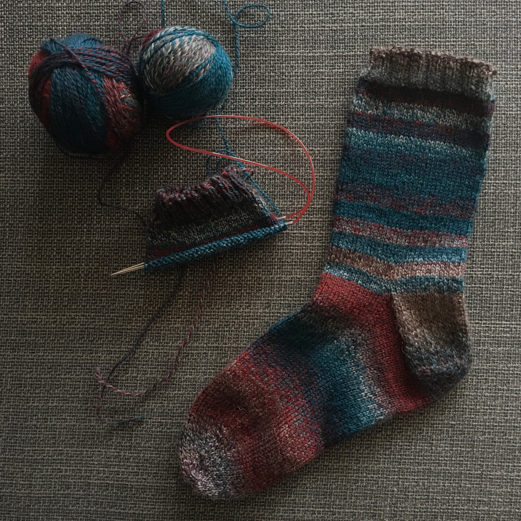 one unfinished handknit sock beside another completed sock in dark blues and reds