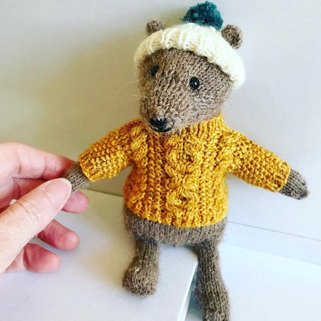 tiny knitted bear in a yellow cabled jumper