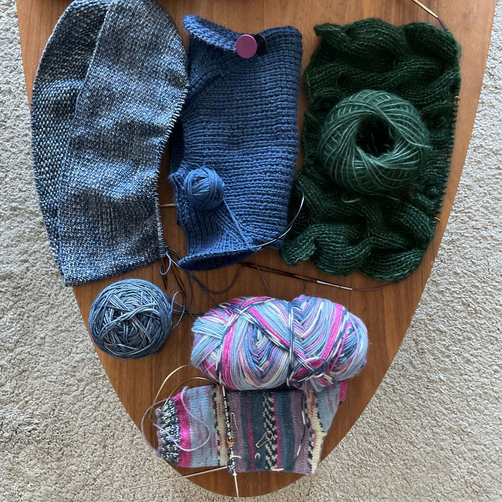 coffee table of unfinished knitting projects