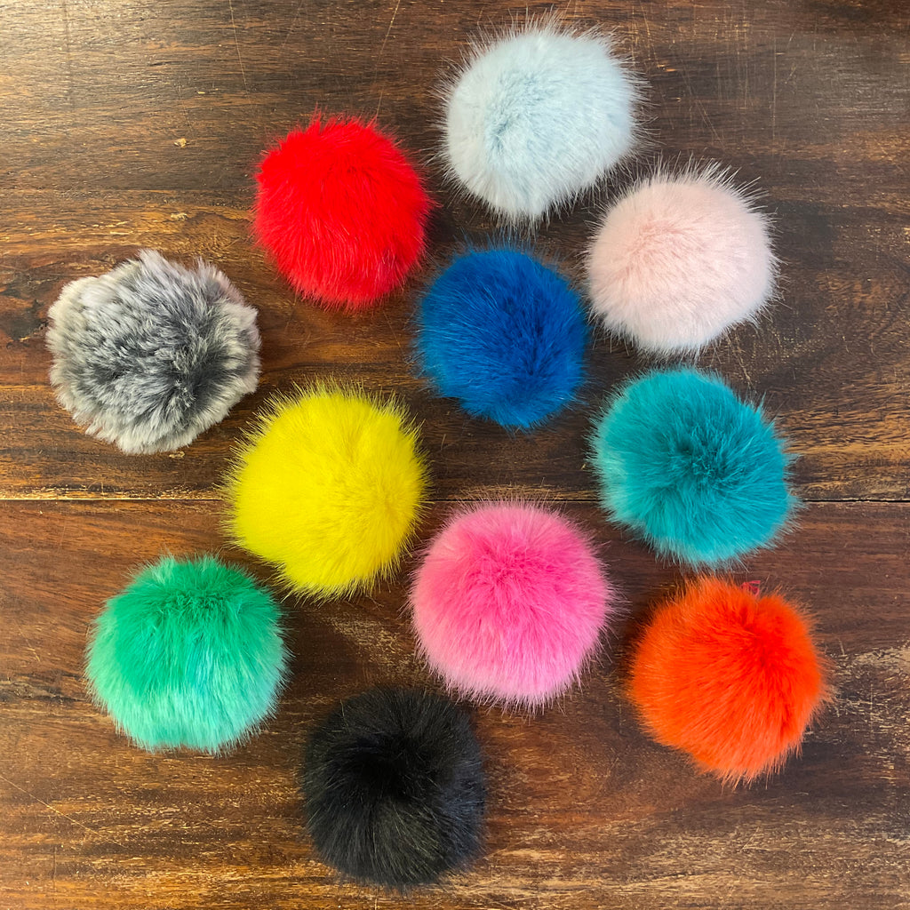brightly coloured faux fur pom poms on a dark wood table