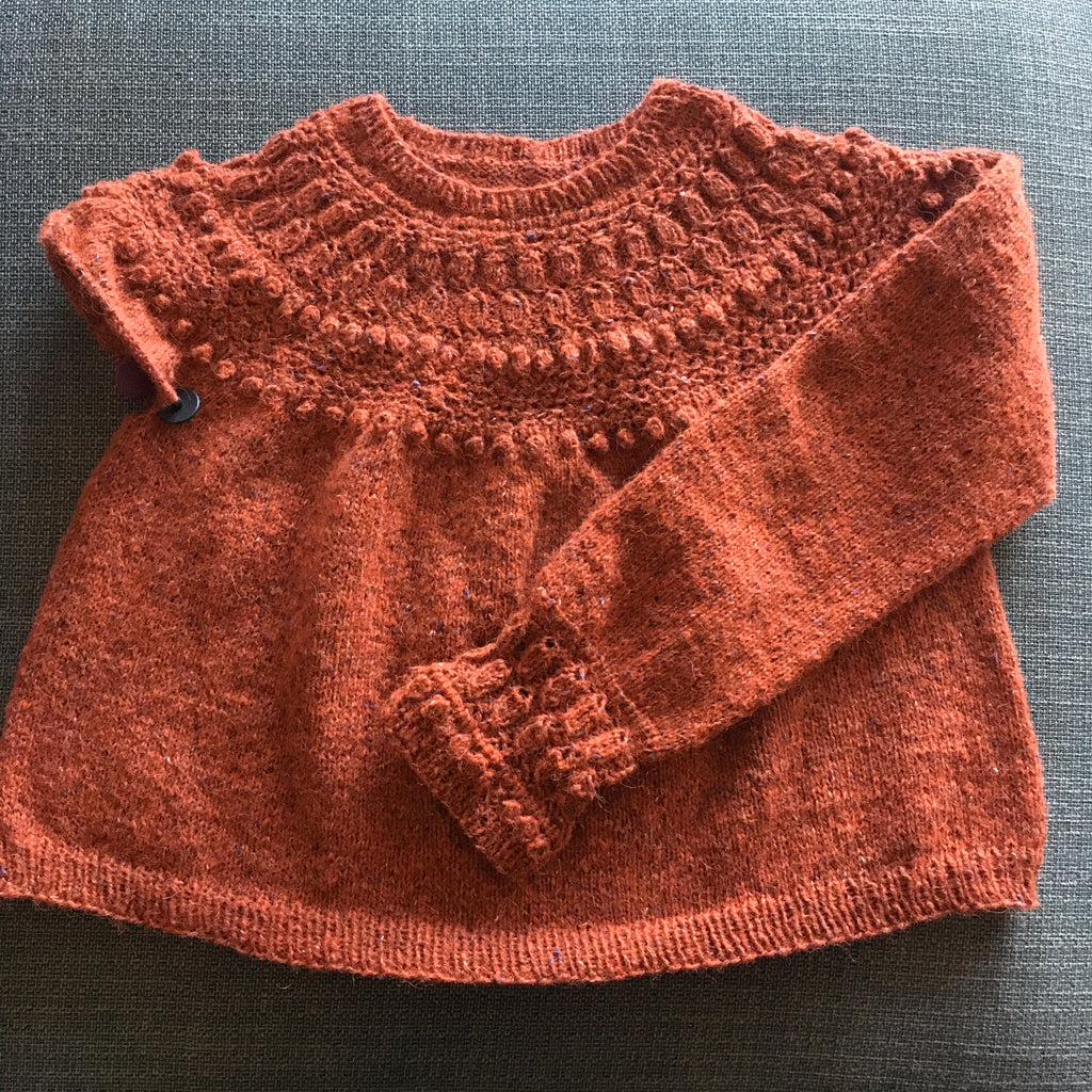 orange hand knitted jumper with one sleeve finished