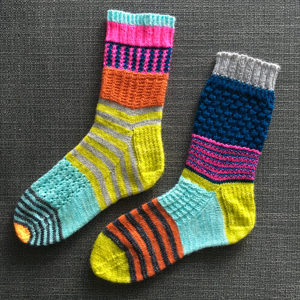 two brightly coloured scrappy hand knit socks