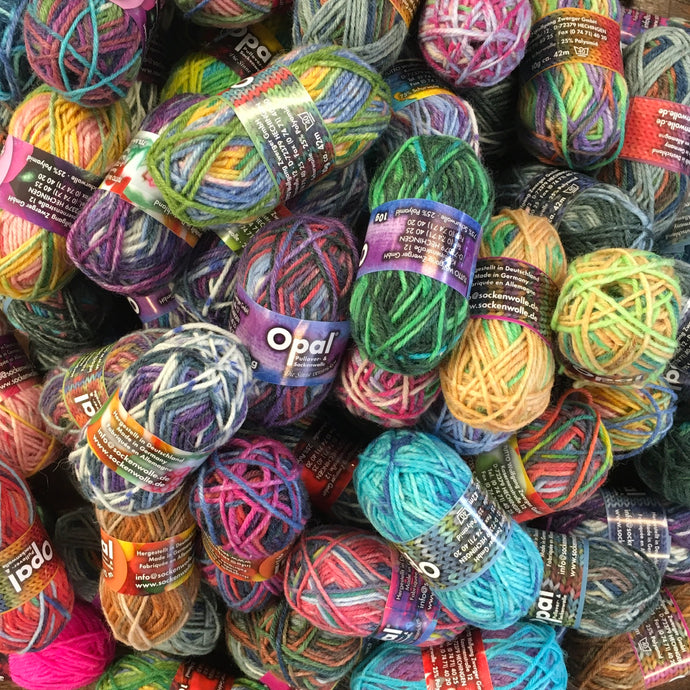A pile of multi coloured mini balls of 4ply yarn